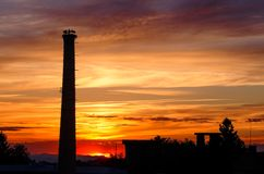 Chimney with the storks. Factory chimney with the storks on nest at sunset Royalty Free Stock Photo