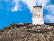Chimney on the straw roof of a wooden house stock photography