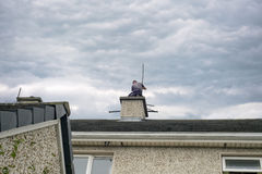 Chimney sweep busy cleaning chimney. On top of a house Stock Image