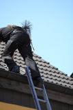 Chimney sweep climbing onto the roof of a house. With his wire brush , rope and tools strapped to his back Royalty Free Stock Photos