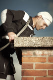 Chimney sweep man checking chimney. Chimney sweep man in work uniform cleaning brick style chimney on building roof Stock Image