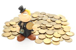 Chimney sweep on a pile of coins. Isolated on white Royalty Free Stock Photos