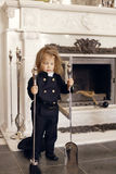 Chimney Sweep Playful Girl. Girl as a chimney sweep against fireplace. Lucky New Year's Eve and New Year Stock Photo