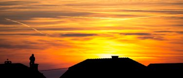 Chimney Sweep on Roof - silhouette. Chimney sweep at work on the rooftop - sunset and silhouette Stock Photo