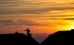 Chimney Sweep on Roof - silhouette. Chimney sweep at work on the rooftop - sunset and silhouette Royalty Free Stock Photos