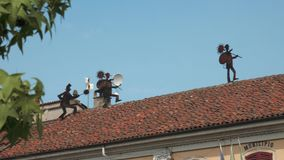 Chimney sweepers sculptures on the roof of town hall, Gravellona Lomellina, PV, Italy.  stock video footage