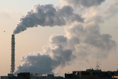 Chimney of thermal power plant at wintertime. City heating causes air pollution Stock Images