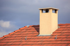 The chimney on top of a red roof Stock Photography