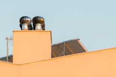 Chimney ventilator fan system on top of a house. Royalty Free Stock Image