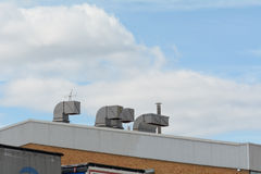 Chimney vents on roof of industrial unit Stock Photos