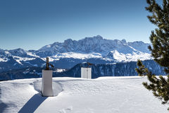 Chimneys of Alpine hut in front of a panorama of snow-capped pea Royalty Free Stock Images