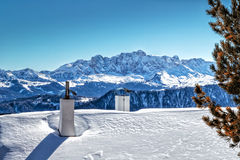 Chimneys of Alpine hut in front of a panorama of snow-capped pea. Chimneys of Alpine chalet in the snow in front of a panorama of snowy peaks on a bright sunny Royalty Free Stock Photography