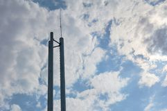 Three chimneys boiler room with antenna on top against a blue sky with clouds. stock images