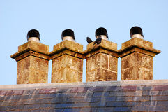 Chimneys and crows. An image of four chimneys with crows on top Royalty Free Stock Photography