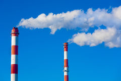 Chimneys with dramatic clouds of smoke. Stock Image