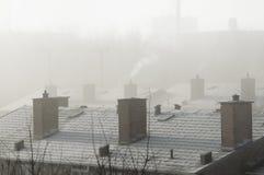 Chimneys with a fog illuminated background. Smoking chimneys on the house tops Stock Photo