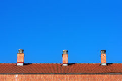 Chimneys on house roof against blue sky Royalty Free Stock Photos
