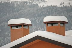 Chimneys of houses covered with snow after snowfall Stock Photography