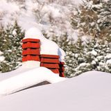 Chimneys of houses covered with snow Stock Photos