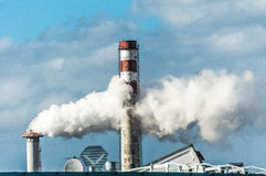 Chimneys of an industrial unit with thick, white smoke blowing out of one chimney Royalty Free Stock Images