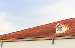 Chimneys on roof of red tiles with blue sky and clouds Royalty Free Stock Images