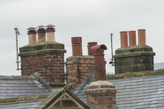 Chimneys on rooftops Stock Images