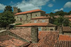 Chimneys on rooftops of old houses. With stone walls and green treetops, in a sunny day at Sortelha. One of the most astonishing and well preserved medieval royalty free stock images