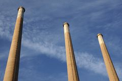 Chimneys. Three chimneys reaching the blue cloudy sky Stock Images