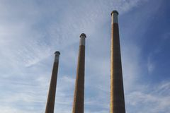 Chimneys. Three chimneys reaching into the blue sky Stock Images
