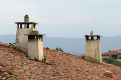 Chimneys. On a tile roof on a background of mountains in the Bulgarian village Royalty Free Stock Photography