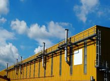 Chimneys on a yellow factory facade under a blue sky with clouds stock images