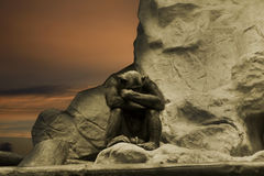 Chimp thinking. On the rock Stock Images