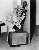 Chimpansee in laag en hoed die met een koffer lopen (Alle afgeschilderde personen leven niet langer en geen landgoed bestaat Leve Stock Afbeelding