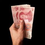 Chinês moderno 100 cédulas de renminbi do yuan na mão masculina Fotos de Stock