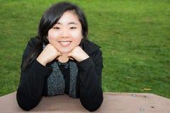 Chin de reclinación adolescente sonriente en las manos Imagen de archivo