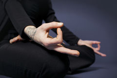 Chin Mudra and lotus posture. Woman practicing yoga in lotus posture (Padmasana) and  fingers in Chin Mudra in black clothes on blue background Royalty Free Stock Photography