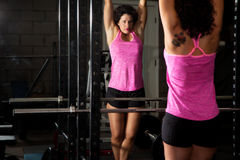 Chin-up Preparation. A fitness trainer looks at herself confidently in the mirror as she prepares to do chin-ups Stock Photos