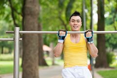 Chin-up. Vietnamese man doing chin-ups outdoors Royalty Free Stock Photography