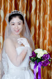 China Beautiful Bride. Wear a wedding dress, wearing a headdress, holding flowers beautiful Chinese bride royalty free stock photography