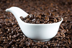 China bowl with coffee beans. White china bowl with roasted coffee beans stock images