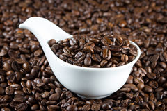 China bowl with coffee beans. White china bowl with roasted coffee beans stock photos