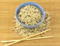 Rice, bowl and chopsticks. China color rice and blue bowl on brown straw mat with chopsticks closeup stock image