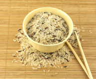 Rice, bowl and chopsticks. China color rise and beige bowl on brown straw mat with chopsticks closeup stock photo