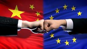 China contra el conflicto de la UE, crisis de las relaciones internacionales, puños en fondo de la bandera imagen de archivo libre de regalías