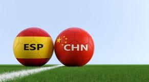 China contra Fósforo de futebol da Espanha - bolas de futebol em cores nacionais de China e de Espanhas em um campo de futebol Fotografia de Stock Royalty Free
