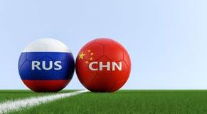 China contra Fósforo de futebol de Rússia - bolas de futebol em cores nacionais de China e de Russias em um campo de futebol Fotos de Stock