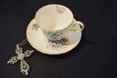 China cup and saucer with a cross royalty free stock photography