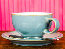 China Cup and Saucer Wirth a Tea Spoon. China Cup and Saucer With a Tea Spoon Against A Pink Background Royalty Free Stock Photos