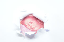 China currency through torn white paper Stock Images
