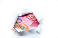 China currency through torn white paper Stock Photos